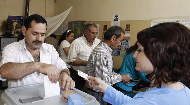 A Syrian man casts his vote at a polling station in Damascus during the parliamentary elections (AP)