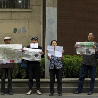 Petitioners hold up protest slogans outside the Beijing hospital where Chen Guangcheng is receiving treatment (AP)