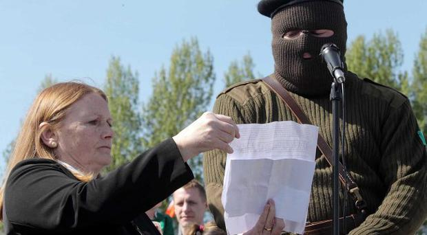 Marian Price holds a statement which was read out by a masked man during a 32 County Sovereignty Movement Easter commemoration in Derry