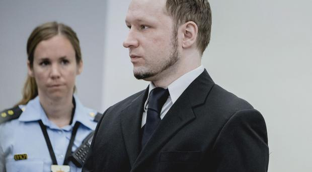 Anders Behring Breivik, who has admitted to the July 22, 2011 massacre and a bombing in Oslo that killed eight people earlier that day, stands with a police woman in court in Oslo Thursday May 10, 2012