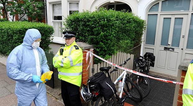 A police forensics officers walks into a house in Wandsworth, south London, after two babies were found dead