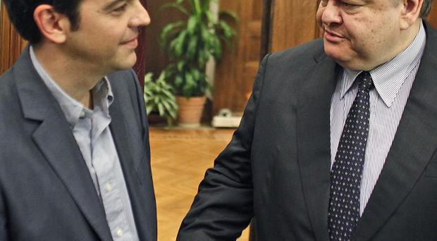 Greece's socialist leader Evangelos Venizelos offers his hand to the leader of the Radical Left Coalition party Alexis Tsipras in Athens (AP)