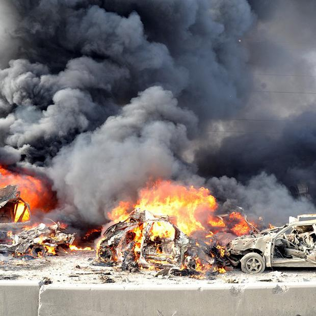 Flames and smoke rise from burning cars after two bombs exploded in the Qazaz neighbourhood of Damascus (AP/SANA)