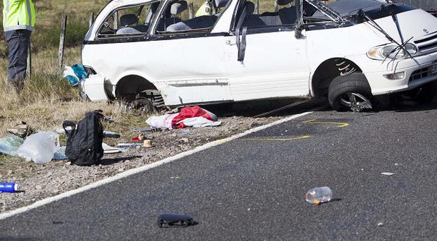 Policemen examine the scene of a minivan crash near Turangi, New Zealand (AP)