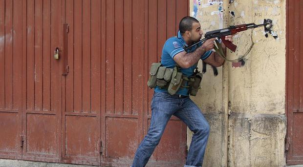 A Sunni gunman fires during clashes, in the northern port city of Tripoli, Lebanon (AP)
