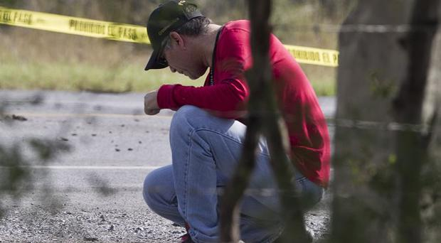 A forensic agent inspects the area where dozens of bodies, some of them mutilated, were dumped on a Mexican highway (AP)