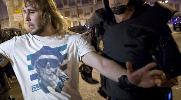 A demonstrator is led away by police officers as he and others are evicted from Puerta del Sol square in Madrid, Spain (AP)