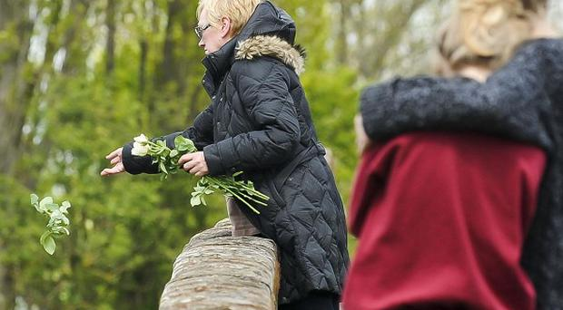 A woman throws floral tributes into the water from a bridge near where the bodies of a man and child were pulled from the River Avon