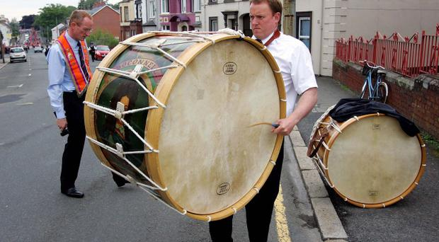 Colin McCusker beats out a steady rhythm as his brother James listens in while tuning the Lambeg drum before the Twelfth parade through Lurgan. The brothers are both members of Boconnell LOL 123. Picture By Rick Hewitt. 12/7/11.