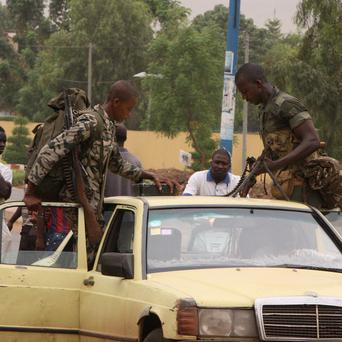 Two soldiers loyal to junta chief Capt Amadou Sanogo load their weapons, including a machine gun, onto a taxi (AP Photo/Harouna Traore)