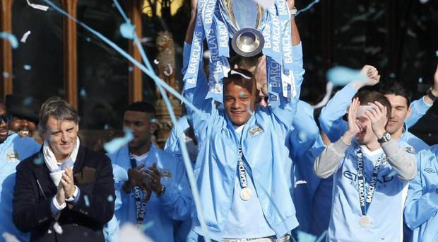 Party on: Manchester City captain Vincent Kompany shows off the Premier League trophy to fans at their city centre victory parade