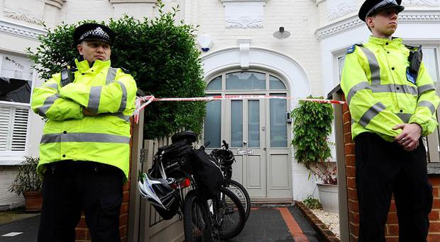Police officers stand outside a house in Wandsworth, south London, after two babies were found dead last week