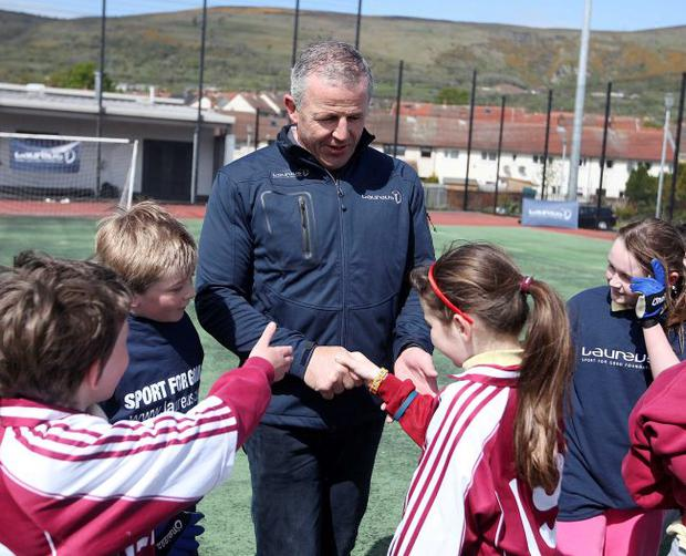 Shake on it: Former New Zealand rugby star Sean Fitzpatrick received a warm welcome at Bunscoil An Tsleibhe Dhuibh Primary School in the Ballymurphy area of Belfast