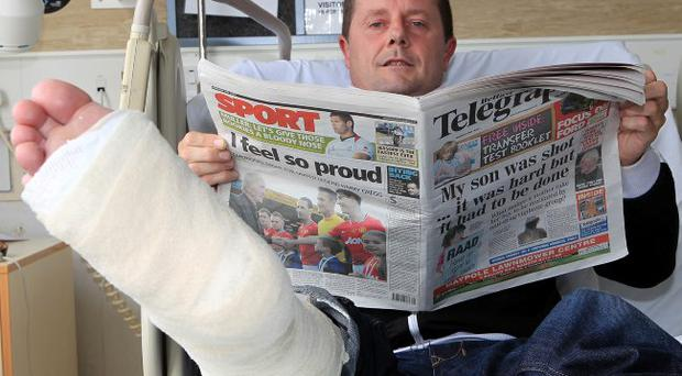 Big break: Manchester United fan David Harper in hospital after breaking his ankle while trying to get a photo of Rio Ferdinand