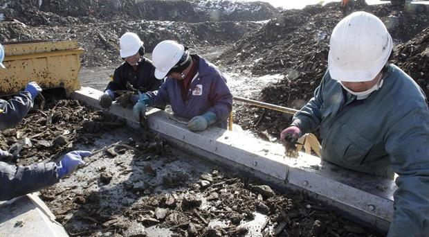 Workers sort debris in Minamisanriku nearly a year after the March 11 tsunami hit the north-eastern Japanese town (AP)