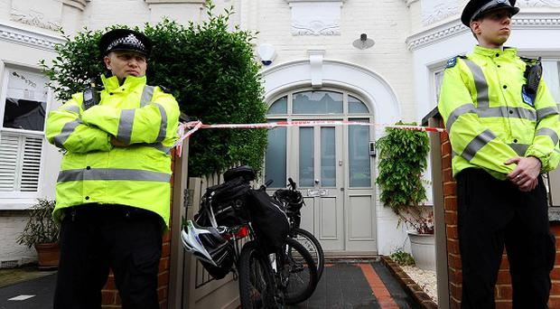 Police officers stand outside the house in Wandsworth where Lily Boots and her brother Mason were found dead