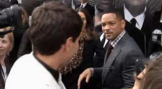 Will Smith walks away from a reporter after slapping him on the red carpet (AP)