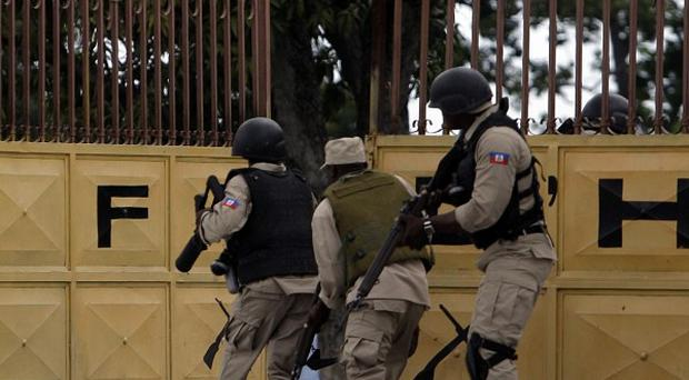 National police officers rush a former army base to arrest members of the dissolved army in Port-au-Prince, Haiti (AP Photo)