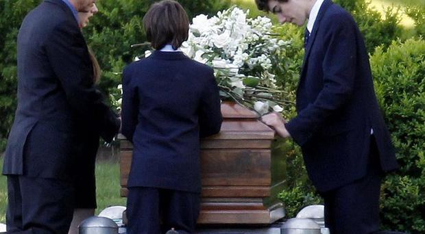 Robert F Kennedy Jr kneels with his children at the casket of Mary Richardson Kennedy (AP Photo)