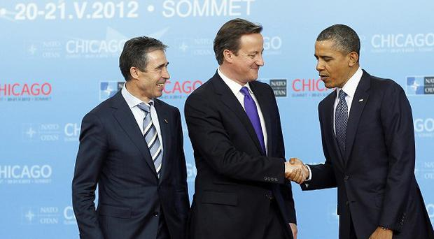 Prime Minister David Cameron shakes hand with US President Barack Obama as Nato secretary general Anders Fogh Rasmussen watches (AP Photo)
