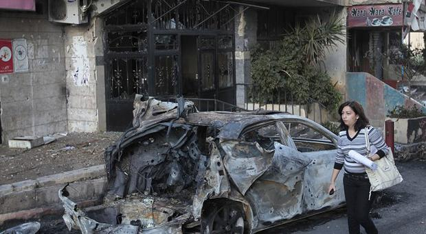 A woman passes a burned car that was damaged during clashes in Beirut (AP)