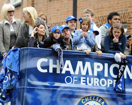 Chelsea players' wives and girlfriends including Frank Lampard's partner Christine Bleakley (centre) follow the team bus during the FA Cup and UEFA Champions League trophy parade in London.