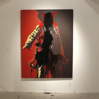 A controversial portrait of South African President Jacob Zuma painted by Brett Murray stands defaced at the Goodman Gallery in Johannesburg (AP)