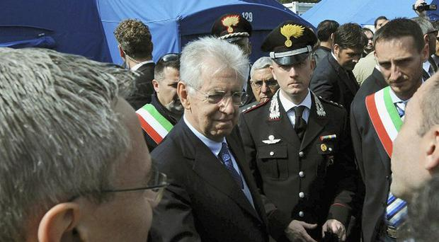 Italian premier Mario Monti visits a tent camp in the village of Finale Emilia, in the area hit by an earthquake (AP)
