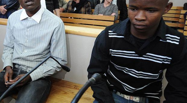 Chris Mahlangu, left, and Patrick Ndlovu sit at the court in South Africa (AP)