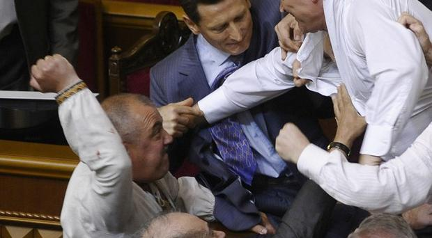 Lawmakers from pro-presidential and oppositional factions fight in the parliament session hall in Kiev, Ukraine (AP)