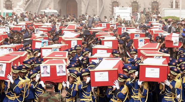 Yemeni officers and soldiers carry coffins of soldiers who were killed in a suicide bomb attack in Sanaa, Yemen (AP)