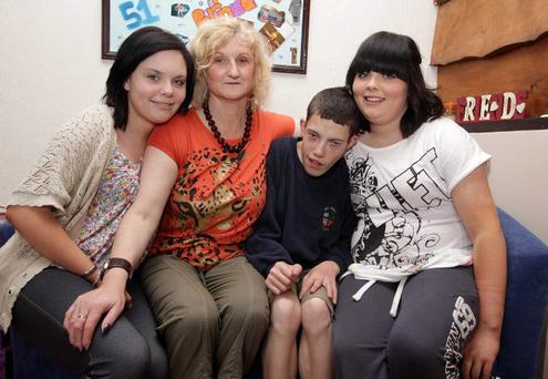 Foster mum Jennifer Burtonwood pictured at her home in Carrickfergus with her twin 16-year-old daughters Annalise(left) and Rebekah along with her foster son Paul.