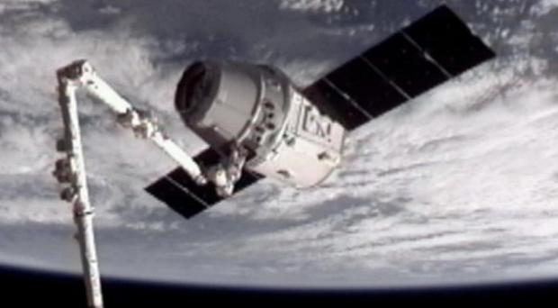 The SpaceX Dragon commercial cargo craft, top, after Dragon was grappled by the robotic arm and connected to the International Space Station (AP/NASA)
