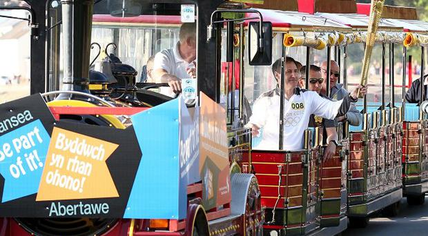 Torchbearer Paul Adams carrying the Olympic flame on a land train on the leg through Swansea