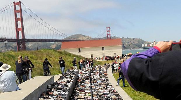 Roberta McLauglin photographs an exhibit of shoes in remembrance of people who have jumped from the Golden Gate Bridge (AP/Noah Berger)