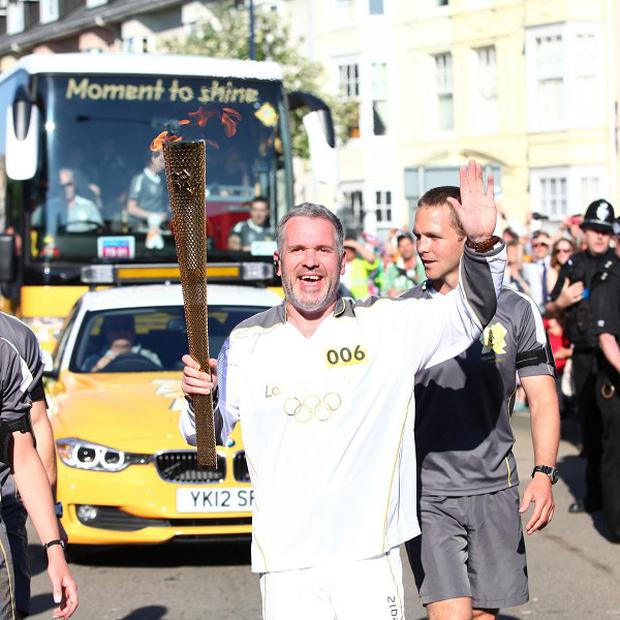 Radio 1 DJ Chris Moyles carries the Olympic Flame on the Torch Relay leg between Aberystwyth and Tre Taliesin