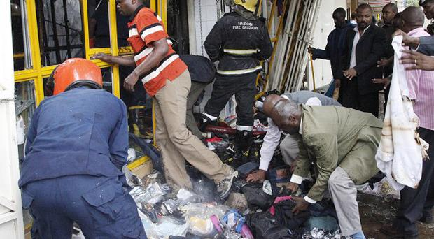 Kenyan firefighters and plain clothes police officers sift through debris after an explosion in Nairobi