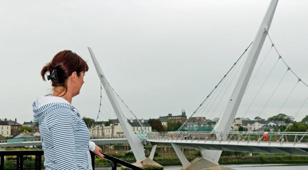 The Peace Bridge towers over the River Foyle