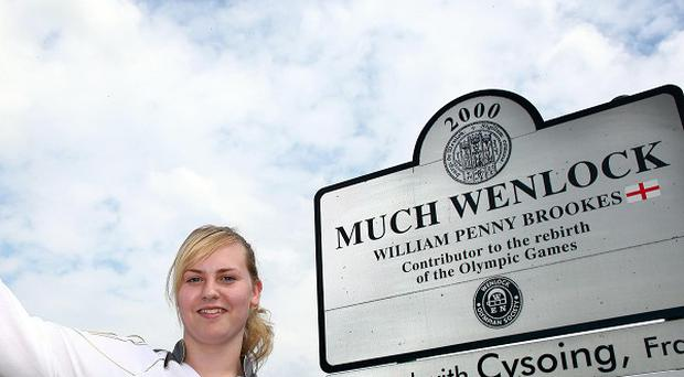 Torchbearer Saffron Allen poses with her Torch in front of the sign for her home village, Much Wenlock