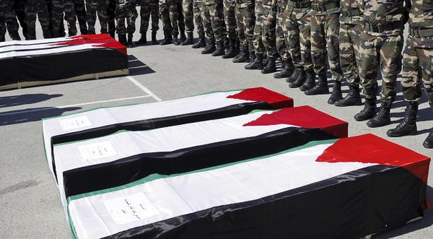 Palestinian security forces stand by the coffins containing the bodies of the Palestinian militants (AP)