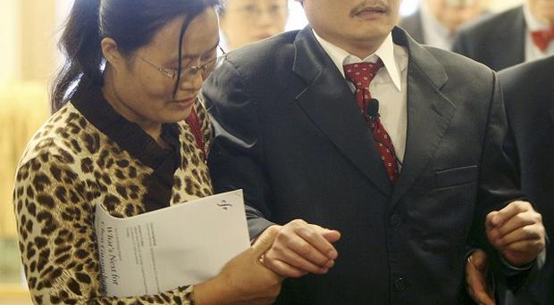 Chen Guangcheng is helped to the stage by his wife, Yuan Weijung, before speaking at the Council on Foreign Relations in New York (AP)