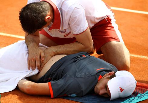 PARIS, FRANCE - MAY 31: Andy Murray of Great Britain receives assistance for a back problem during a break in his men's singles second round match against Jarkko Nieminen of Finland during day five of the French Open at Roland Garros on May 31, 2012 in Paris, France. (Photo by Matthew Stockman/Getty Images)