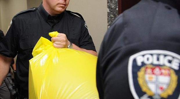 Police remove a package from the Conservative Party headquarters in Ottawa, Ontario, after a human foot was delivered to the building (AP)
