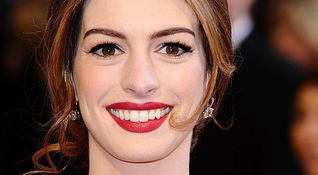 Anne Hathaway has an injured arm to go with her shorn locks