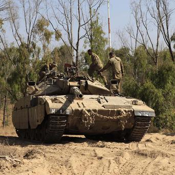 Israeli soldiers man a tank position at the border with Gaza (AP)