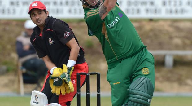 Limavady wicket-keeper Zweshan Malik watches as Neil Russell of North Down hits one for six