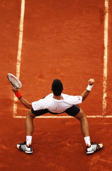 PARIS, FRANCE - JUNE 05: Novak Djokovic of Serbia celebrates victory in his men's singles quarter final match against Jo-Wilfried Tsonga of France during day 10 of the French Open at Roland Garros on June 5, 2012 in Paris, France. (Photo by Matthew Stockman/Getty Images)