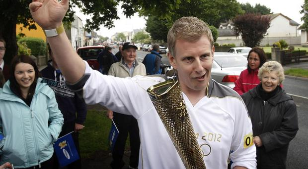 Patrick Kielty holding the Olympic Flame before he completes his leg through Dundrum on Day 20 of the London 2012 Olympic Torch Relay