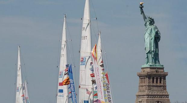 Homeward bound: the Londonderry-Derry clipper leads the flotilla of racing yachts as it sails past the Statue of Liberty in New York