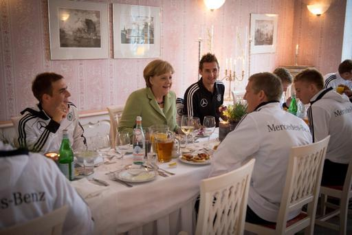 SOPOT, POLAND - JUNE 06: In this photo provided by the German Government Press Office (BPA), German Chancellor Angela Merkel talks to German National Team players Philipp Lahm (L), Miroslav Klose (C) and Bastian Schweinsteiger during a shared dinner at the Euro 2012 Team Hotel on June 6, 2012 in Sopot, Poland. (Photo by Guido Bergmann/Bundesregierung-Pool via Getty Images)